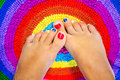 Female legs with a color pedicure feet on colorful rug Royalty Free Stock Photos