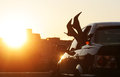 Female legs out car window on background summer sunset. Summer vacations concept.