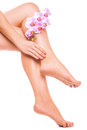 Female legs and pink manicure with orchid flower relaxing pedicure a Royalty Free Stock Images