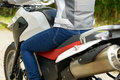 Female legs wearing blue jeans sitting on motorcycle Royalty Free Stock Photo
