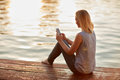 Female with cellphone sitting on river's dock Royalty Free Stock Photo