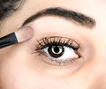 Female lying final touch of makeup at extreme closeup Royalty Free Stock Photo