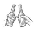 Female and male hands holding and clinking open beer bottles. Royalty Free Stock Photo