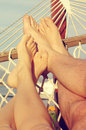 Female and male legs in a hammock on the beach against the sea in a summer sunny day. Royalty Free Stock Photo