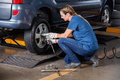 Female mechanic fixing car tire with pneumatic wrench at auto repair shop Stock Photo