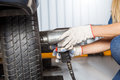 Female mechanic using pneumatic wrench to fix tire cropped of car at repair shop Royalty Free Stock Photos