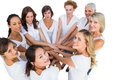 Female models joining hands in a circle and looking at camera on white background Stock Images