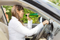 Female motorist drinking and driving while being watched from outside by a young boy Royalty Free Stock Photo