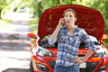 Female motorist phoning for help after breakdown on country road Royalty Free Stock Images