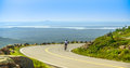 Female mountain bike cyclist riding downhill along cadillac mountain road acadia national park clear summer day panoramic view Stock Images