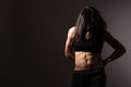 Female muscular body strong fit woman showing her abs unrecognizable dark background Stock Photography