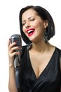 Female musician with closed eyes handing mic portrait of wearing black evening dress and keeping microphone isolated on white Royalty Free Stock Images