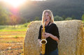 Female musician playing a tenor saxophone attractive as she leans against round hay bale outdoors in an agricultural field Royalty Free Stock Photos