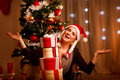 Female near Christmas tree with tower of presents Royalty Free Stock Image
