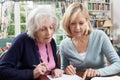 Female Neighbor Helping Senior...
