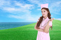 Female nurse with stethoscope with green grass field Royalty Free Stock Photo