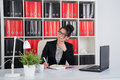 Female office worker business woman in an behind a desk with a phone Stock Images