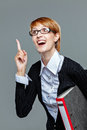 Female office worker holding a folder and gesturing with her finger isolated on grey Stock Image