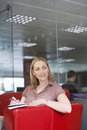 Female office worker sitting on sofa portrait of a smiling casual young executive in Royalty Free Stock Images