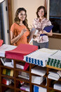 Female office workers standing in mailroom Royalty Free Stock Photo