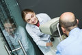 Female optician doing eye examination with aid of slit lamp young positive Royalty Free Stock Images