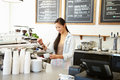 Female owner of coffee shop making a Stock Image