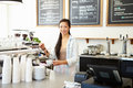Female owner of coffee shop smiling to camera Stock Photo