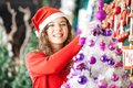 Female owner decorating christmas tree in store portrait of happy beautiful Royalty Free Stock Photo