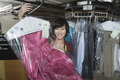 Female owner displaying clean dress in laundry portrait of happy Royalty Free Stock Photography