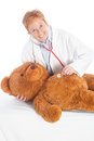 Female paediatrician with teddy pediatrician or doctor a bear making a medical checkup a stethoscope Royalty Free Stock Image