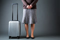 Female passenger and a suitcase in skirt standing next to gray Stock Photography