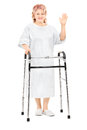 Female patient with walker waving with hand full length portrait of a isolated on white background Stock Image