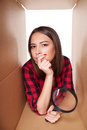 Female peeking into carton box looking through magnifying glass Royalty Free Stock Photo