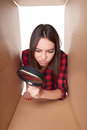 Female peeking into carton box looking through magnifying glass young with suspicion Royalty Free Stock Images