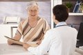 Female pensioner at doctors office listening to doctors explanation Royalty Free Stock Image