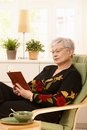Female pensioner reading at home wearing glasses sitting in armchair Stock Photos
