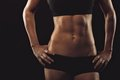 Female with perfect abdomen muscles close up of fit woman s torso her hands on hips on black background Royalty Free Stock Images