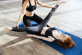 Female personal trainer helping girl in leg stretching workout