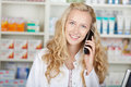 Female pharmacist communicating on cordless phone portrait of happy in pharmacy Royalty Free Stock Images