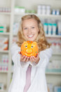 Female pharmacist holding piggy bank portrait of in pharmacy Royalty Free Stock Image