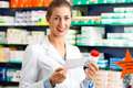 Female pharmacist in pharmacy with medicament Royalty Free Stock Photo