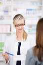 Female pharmacist talks about prescription to patient the medical inside the pharmacy Royalty Free Stock Photos
