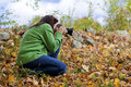 Female photographer crouching in fall leaves to take a picture Royalty Free Stock Photo