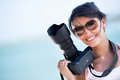 Female photographer professional holding a camera and smiling Stock Photography