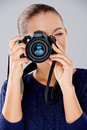Female photographer taking a photo with professional dslr camera pointing the lens directly at the viewer Stock Image