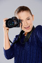 Female photographer taking a photo with professional dslr camera pointing the lens directly at the viewer Royalty Free Stock Images