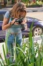 Female photographing flowers on the street wearing blue jeans Royalty Free Stock Photo