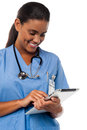 Female physician holding tablet pc in uniform operating device Royalty Free Stock Image