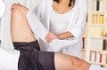 Female physio therapist hands working on male patients lower leg and ankle, bending knee, blurry clinic background Royalty Free Stock Photo