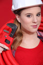 Female plumber in red with a pipe and wrench Royalty Free Stock Photo
